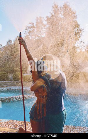Couple having fun pour each other with garden hose - Stock Photo