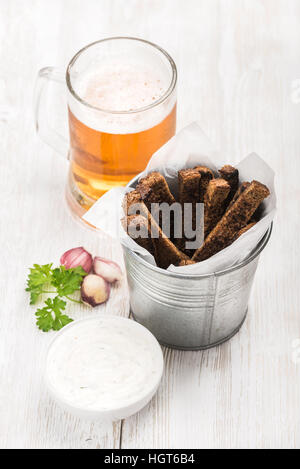 Beer snack set. Pint of pilsener in mug and rye bread croutons with garlic cream cheese sauce, fresh parsley over - Stock Photo
