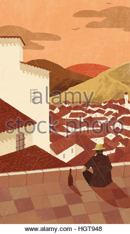 Man with bottle of wine relaxing watching sunset over idyllic village - Stock Photo