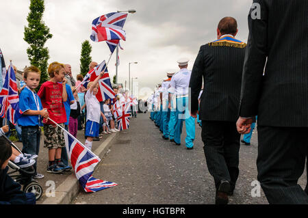 Children wave union flags and Northern Ireland flags during an Orange Order parade. - Stock Photo