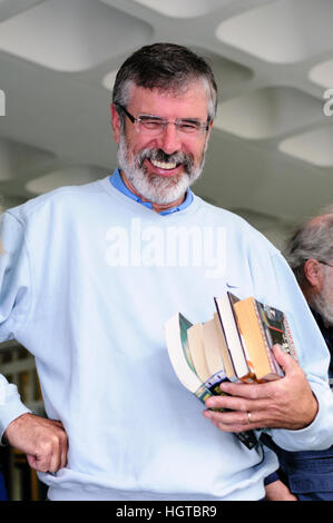 Gerry Adams laughs as he buys books in a book sale in Belfast. - Stock Photo