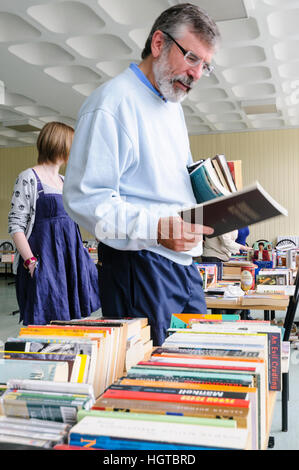 Gerry Adams peruses books at a book sale in Belfast. - Stock Photo