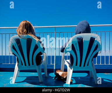Two passengers sitting in plastic chairs on the deck of a passenger ship looking out to sea on a calm summer day - Stock Photo