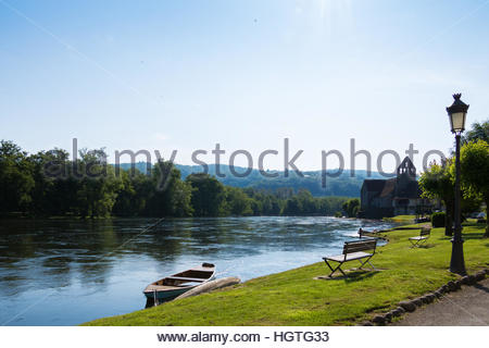 Travel destination France, Dordogne river shore Beaulieu-sur-Dordogne boats on river idyllic scene, peaceful landscape - Stock Photo