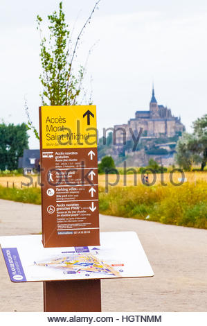 Visitor Sign showing the way to (or Acces) to Mont Saint Michel,(along with a map) & Mont St Michel in Normandy, - Stock Photo