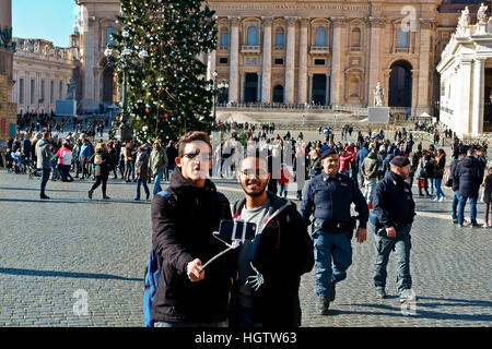 Two friends taking saelfie using smartphone with stick at Saint Peter's Square (Piazza San Pietro) Vatican City, - Stock Photo
