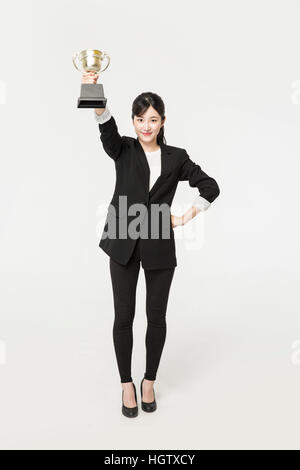 Young smiling businesswoman with trophy posing - Stock Photo