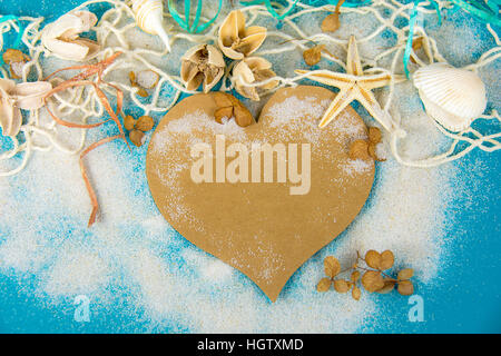 brown heart and seashells in net and sand on turquoise painted wood - Stock Photo