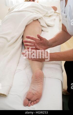 A masseuse massaging a clients leg - Stock Photo