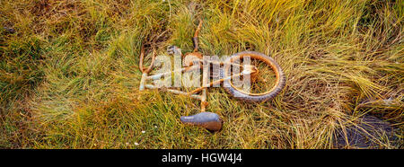 A broken children's bike rusting in ditch beside an airfield in an arctic village. - Stock Photo