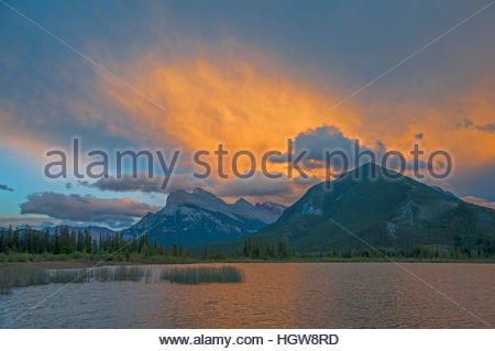 A sunset lights clouds over Mount Rundle, Sulphur Mountain and Vermillion Lakes. - Stock Photo