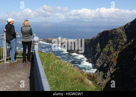 Man and women looking out from clifftop viewpoint in Ireland with white waves,, blue sky at The Fogher Cliffs, Valentia - Stock Photo