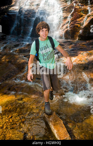 A man hiking at Arethusa Falls in Crawford Notch State Park in New Hampshire's White Mountains. - Stock Photo