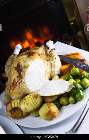 Whole Roast Chicken with potatoes and fresh cooked vegetables ready for serving. - Stock Photo