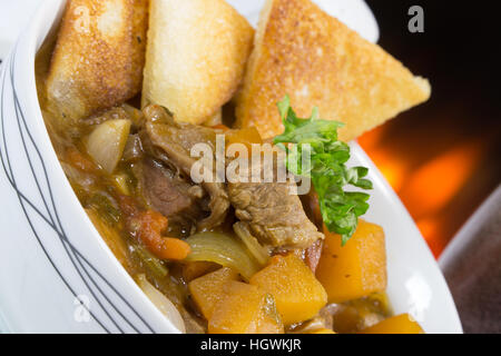 An English pub/restaurant bowl of Beef Casserole served with fried bread croutons.