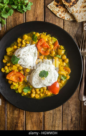 Indian chickpeas with poached eggs and chapatis bread - Stock Photo