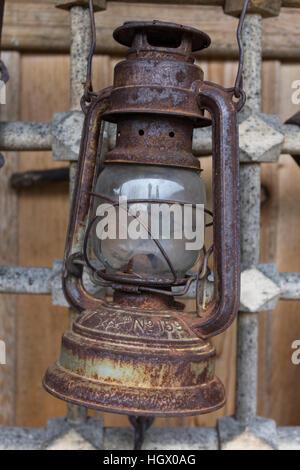 Old rusty kerosene lamp hanging on a metal grid in bulgarian village Zheravna - Stock Photo