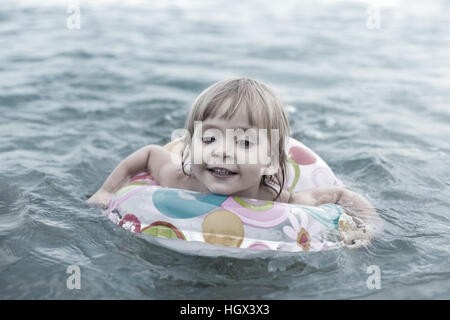 Child is swimming on a circle - Stock Photo