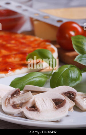 preparation of ingredients for pizza: sliced mushrooms, basil, dough, tomato. Vertical - Stock Photo
