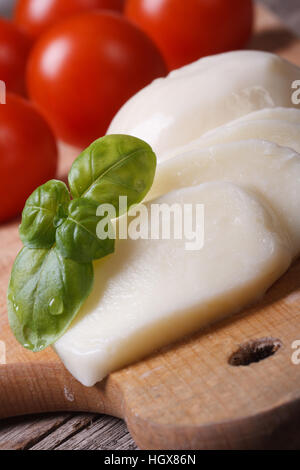 macro sliced mozzarella and green basil on a background of red cherry tomatoes. vertical - Stock Photo