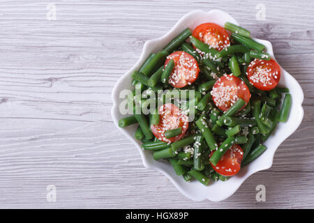 Salad of green beans, cherry tomatoes and sesame seeds in a beautiful white plate. horizontal. top view - Stock Photo