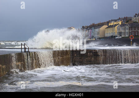 A winter storm buffets a harbor wall sending waves foam and spray into the air and curtains of water cascading into - Stock Photo