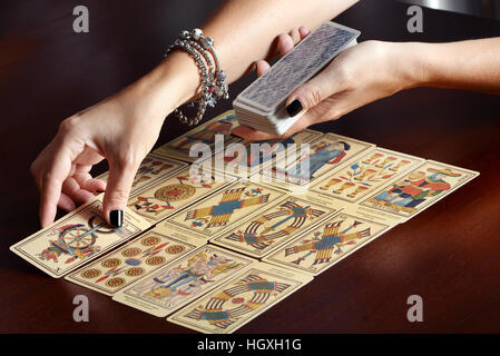 Female fortune tellers hands spreading vintage tarot cards on dark table surface - Stock Photo
