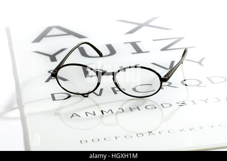 Black oval glasses laying over white glossy eye chart table, sight test optometry concept - Stock Photo