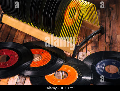 Classical vinyl singles and a record stand on a wooden floor - Stock Photo