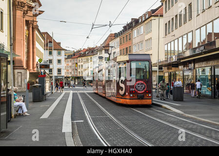 An electric tram and people on foot in a street in the city center of Wurzburg, Bavaria, Germany. - Stock Photo