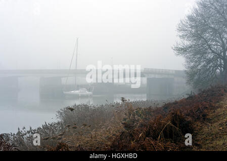 yacht exiting lock thick winter fog at Chatelier Lock Le Lyvet Rance Valley River Rance Brittany France - Stock Photo