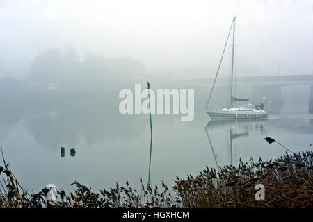 starboard navigation pole and yacht thick winter fog below Chatelier Lock Le Lyvet Rance Valley River Rance Brittany - Stock Photo