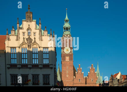 Wroclaw town hall clock tower and adjacent traditional building in early evening light, Wroclaw, Poland - Stock Photo