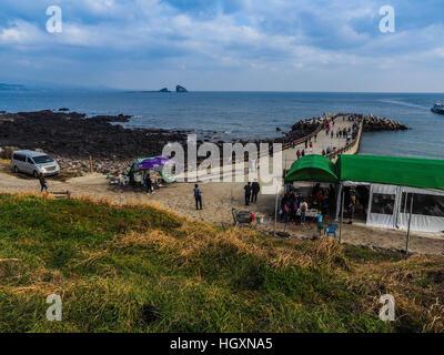 The tourist visited Seongaksan coast, the famous coastal drive with breathtaking scenic views in Jeju island - Stock Photo