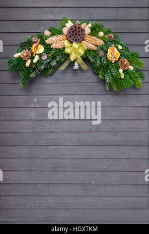 Christmas and winter wreath with yellow bow hanging on dark wooden door - Stock Photo