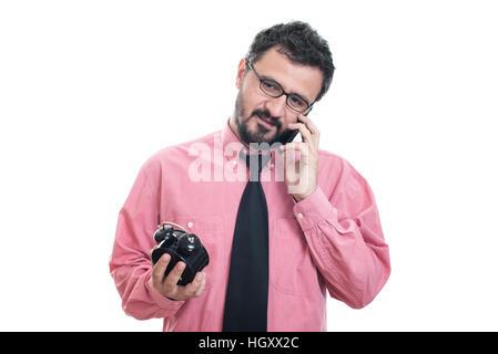 Smiling man with alarm clock talking at his smart phone - Stock Photo