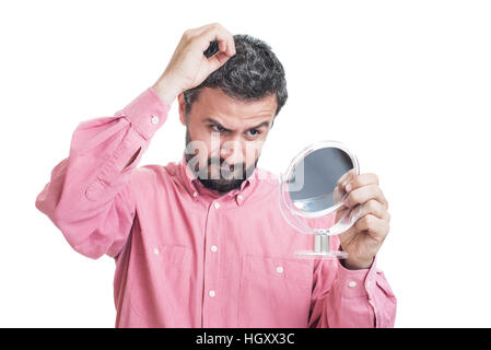 Man worried about gray hair looking in a mirror - Stock Photo
