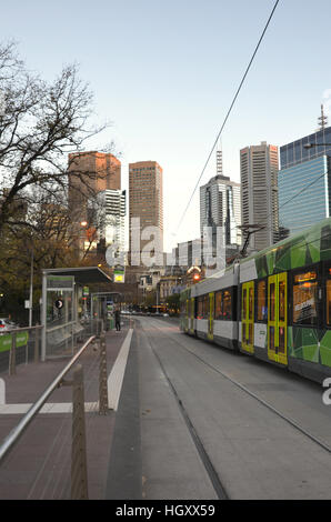 View along tramlines and tram with skyscrapers in the background in Melbourne, Australia - Stock Photo