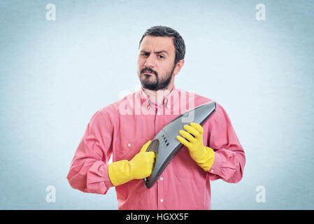Young man with handheld vacuum cleaner - Stock Photo