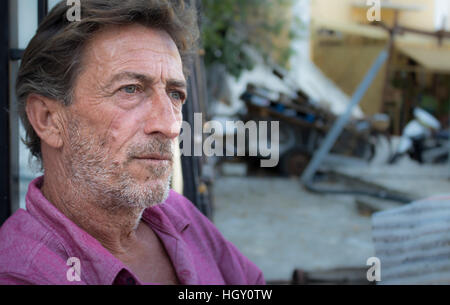 Portrait of a senior man who used to work as sailor sitting outside his shop, Symi Island, Greece. - Stock Photo