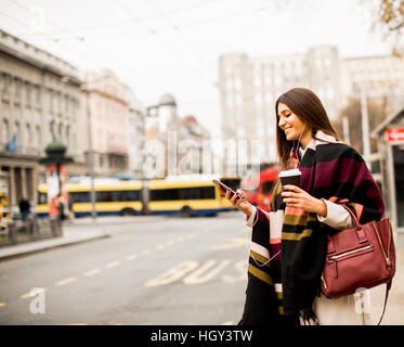 View at young woman hailing a taxi on the street in the city - Stock Photo