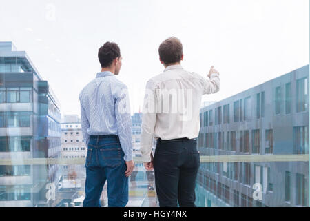 Two business people talking and looking at the horizon, one person pointing at something. Concept about projects, - Stock Photo