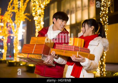 Happy young couple with new year gifts - Stock Photo