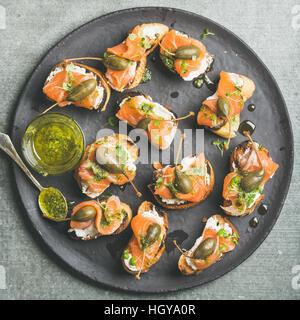 Homemade salmon crostini in black plate over grey background - Stock Photo