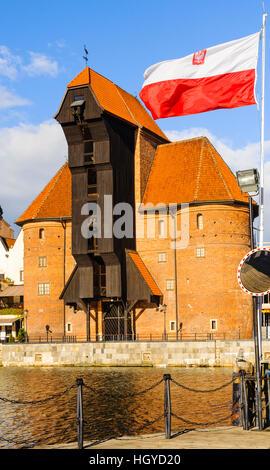 Polish flag and Żuraw or Crane on the waterfront of Główne Miasto (Main Town) Gdansk Poland - Stock Photo