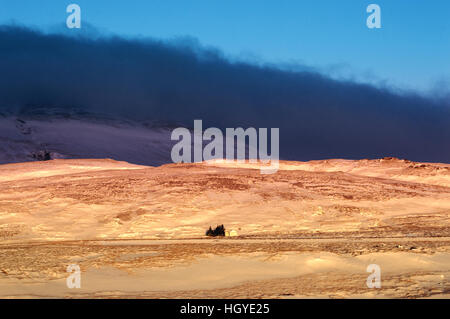 A small house in the sunlight under dark blue clouds in an Icelandic winter landscape - Stock Photo