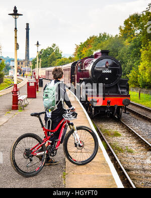 Woman with bicycle as steam train approaches at Rawtenstall on the East Lancashire Railway - Stock Photo