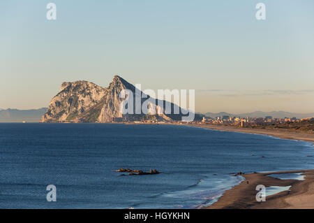 View of The Rock of Gibraltar and La Linea de la Concepcion as seen from the Mediterranean coast in the early morning - Stock Photo