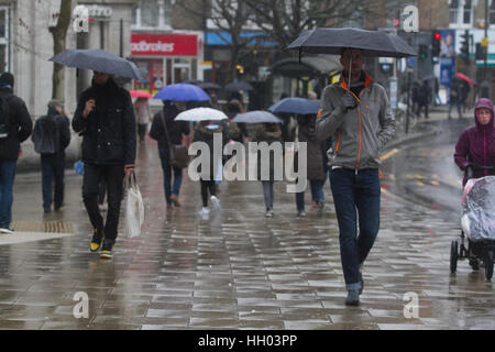 Wimbledon London, UK. 15th Jan, 2017. Pedestrians shelter from the cold rain in Wimbledon town centre Credit: amer - Stock Photo