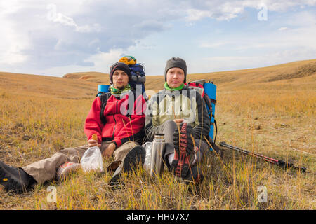 Couple man and woman tourists make selfie backpacks sitting on the grass. - Stock Photo
